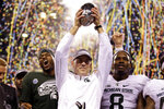 FILE - In this Dec. 5, 2015, file photo, Michigan State coach Mark Dantonio holds the trophy after Michigan State defeated Iowa 16-13 in the Big Ten championship NCAA college football game in Indianapolis. Dantonio announced his retirement Tuesday, Feb. 4, 2020, ending a 13-year run in which he guided the Spartans to heights they hadn't reached in decades. (AP Photo/Michael Conroy, File)