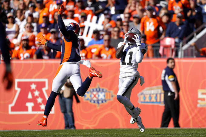 Las Vegas Raiders wide receiver Henry Ruggs III (11) pulls in a touchdown pass as Denver Broncos free safety Justin Simmons defends during the first half of an NFL football game, Sunday, Oct. 17, 2021, in Denver. (AP Photo/David Zalubowski)