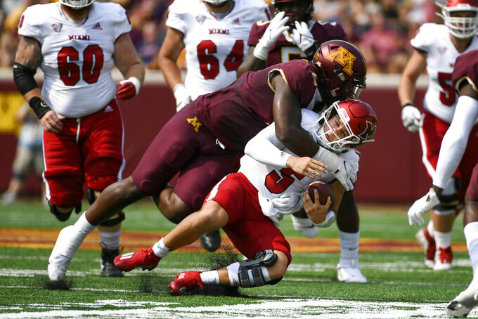 Miami-Ohio quarterback Brett Gabbert (5) is tackled by Minnesota defensive lineman Thomas Rush on a short run during the first half of an NCAA college football game on Saturday, Sept. 11, 2021, in Minneapolis. (AP Photo/Craig Lassig)
