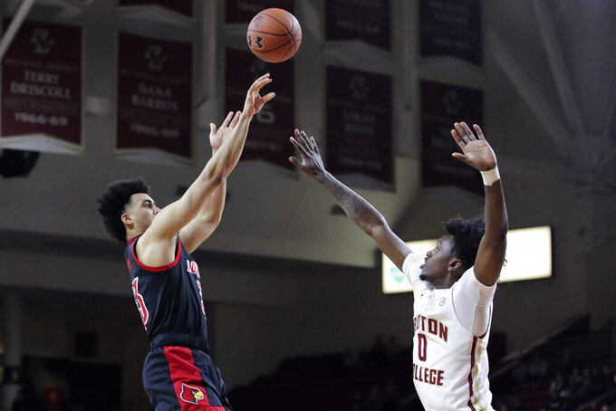 Louisville forward Jordan Nwora, left, shoots over Boston College forward CJ Felder during the first half of an NCAA college basketball game in Boston, Wednesday, Jan. 29, 2020. (AP Photo/Charles Krupa)