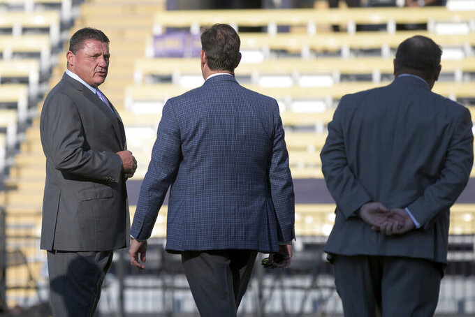 LSU coach Ed Orgeron, left, arrives before the team's NCAA college football game against McNeese State in Baton Rouge, La., Saturday, Sept. 11, 2021. (AP Photo/Matthew Hinton)