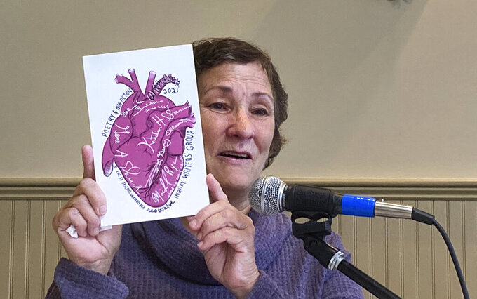Debi Gevry-Ellsworth, of Pomfret, Conn., who lived as a child at the St. Joseph's Orphanage, holds a book of poems and essays, Thursday Sept. 16, 2021, in South Burlington, Vt. Gevry-Ellsworth attended a reunion of former residents of the closed Vermont orphanage, where former residents gathered to seek ways to recover from the abuse that many say they suffered at the orphanage. Gevry-Ellsworth said writing her portion of the book helped her move forward. (AP Photo/Wilson Ring)