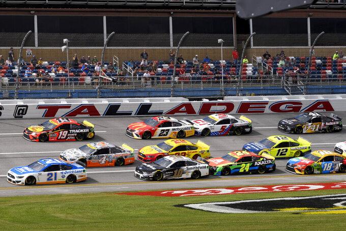 Matt DiBenedetto (21) Martin Truex, Jr. (19) and Kevin Harvick (4) lead an early lap during a NASCAR Cup series auto race Monday, Oct. 4, 2021, in Talladega, Ala. (AP Photo/John Amis)