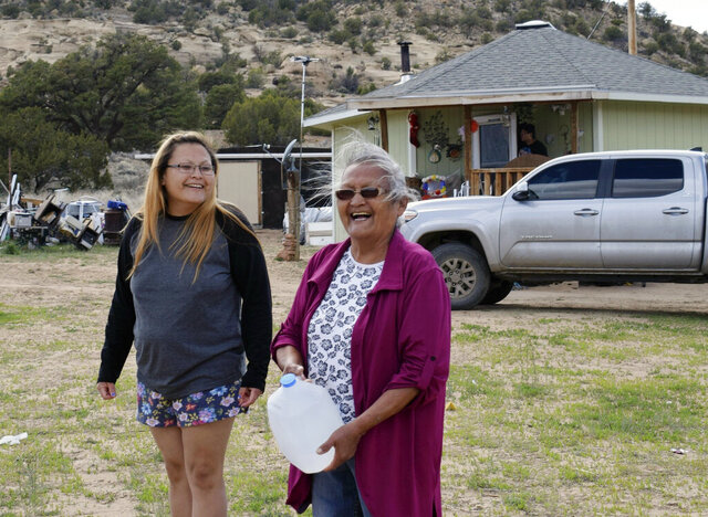 This photo taken April 24, 2020, shows Wynice Franklin, left, and her mother Louise Johnson, right, receiving bottled water from local officials in Church Rock, N.M. Johnson said her biggest challenge during the coronavirus pandemic is getting water to her home. (Vida Volkert,/Gallup Independent via AP)