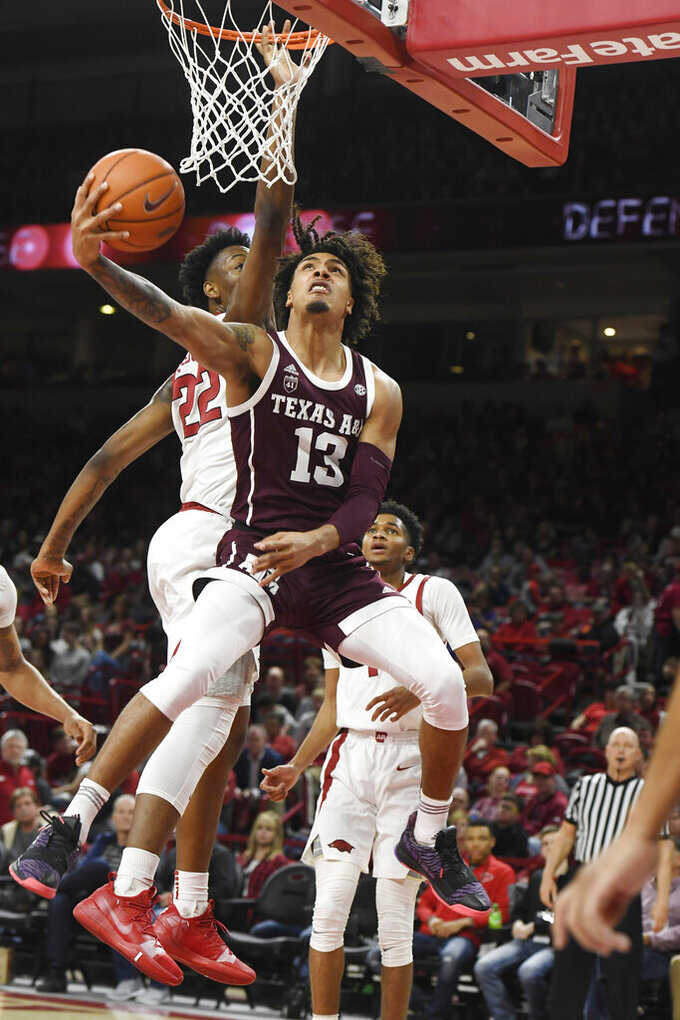 Texas A&M guard Brandon Mahan (13) drives past Arkansas defender Gabe Osabuohien during the second half of an NCAA college basketball game, Saturday, Feb. 23, 2019 in Fayetteville, Ark. (AP Photo/Michael Woods)