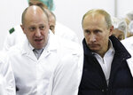 FILE - In this Sept. 20, 2010, file photo, businessman Yevgeny Prigozhin, left, shows Russian President Vladimir Putin around his facility that produces school meals outside St. Petersburg, Russia. Scores of children were diagnosed with dysentery after eating food at several state-run day care centers in Moscow in December 2018. Their parents have filed suit against a catering company controlled by Prigozhin, a Putin ally. His company denies it is to blame for the dysentery outbreak. (Alexei Druzhinin/Pool Photo via AP, File)