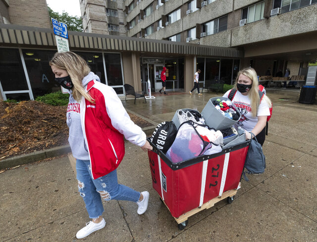 Freshmen Lauren Tamborini and Bailey Donahue move out of Sellery Residence Hall Thursday, Sept. 10, 2020, the University of Wisconsin in Madison, Wis. The students plan on attending class online. Citing rapidly rising COVID-19 cases including two straight days in which one in five student tests came back positive, University of Wisconsin-Madison Chancellor Rebecca Blank locked down the state's largest university campus for two weeks. (Mark Hoffmann/Milwaukee Journal-Sentinel via AP)