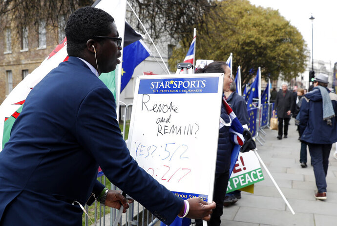 A bookmaker puts up a small white board showing the latest odds on Brexit near the media compound outside the Houses of Parliament in London, Tuesday, March 26, 2019. British Prime Minister Theresa May's government says Parliament's decision to take control of the stalled process of leaving the European Union underscores the need for lawmakers to approve her twice-defeated deal. (AP Photo/Alastair Grant)