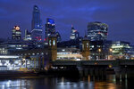 A pumpkin is illuminated on Tower 42 to celebrate Halloween, in the City of London, early Saturday Oct. 31, 2020.  Other buildings include, 20 Fenchurch Street known as The Walkie-Talkie shown back right, The Shard at back centre. (John Walton/PA via AP)
