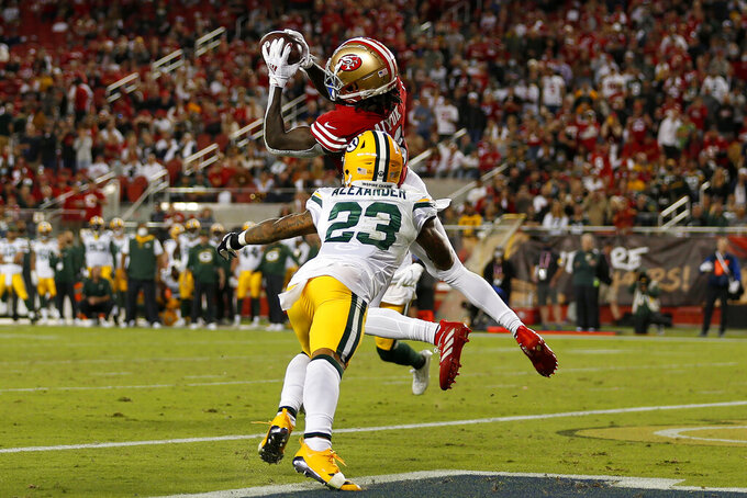 San Francisco 49ers wide receiver Brandon Aiyuk, top, catches a touchdown pass in front of Green Bay Packers cornerback Jaire Alexander (23) during the second half of an NFL football game in Santa Clara, Calif., Sunday, Sept. 26, 2021. (AP Photo/Jed Jacobsohn)
