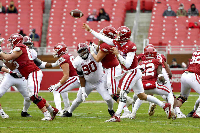 Arkansas quarterback Feleipe Franks (13) throws a pass as Alabama defensive lineman Stephon Wynn Jr. (90) puts on the pressure during the second half of an NCAA college football game Saturday, Dec. 12, 2020, in Fayetteville, Ark. (AP Photo/Michael Woods)