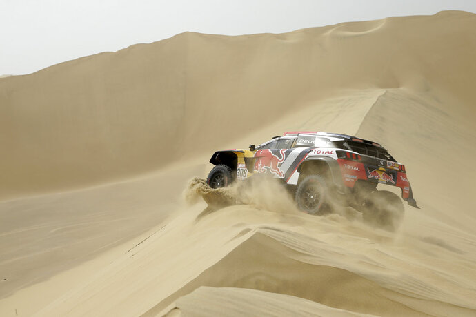 Driver Cyril Despres, of France, and co-driver David Castera, of France, race their Peugeot during the first stage of the 2018 Dakar Rally between Lima and Pisco, Peru, Saturday, Jan. 6, 2018. (AP Photo/Ricardo Mazalan)