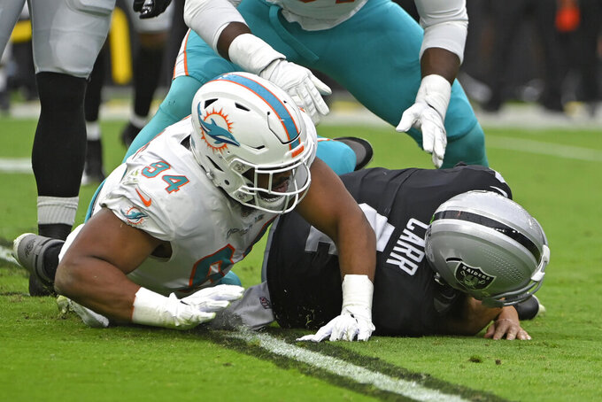 Miami Dolphins defensive end Christian Wilkins (94) sacks Las Vegas Raiders quarterback Derek Carr (4) during the first half of an NFL football game, Sunday, Sept. 26, 2021, in Las Vegas. (AP Photo/David Becker)