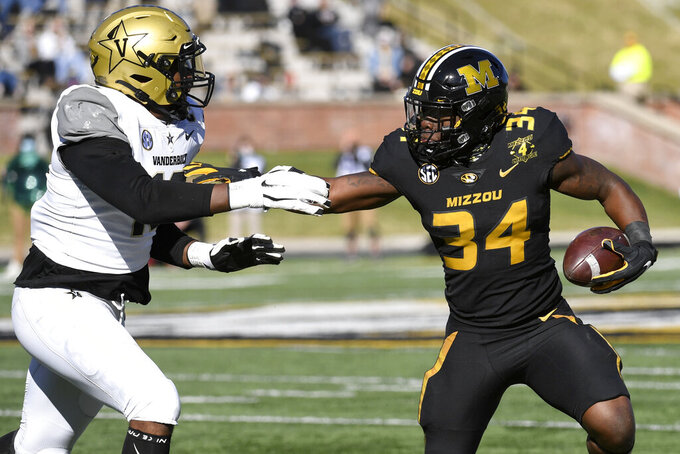 Missouri running back Larry Rountree III (34) runs with the ball as Vanderbilt defensive lineman Dayo Odeyingbo (10) defends during the first half of an NCAA college football game Saturday, Nov. 28, 2020, in Columbia, Mo. (AP Photo/L.G. Patterson)