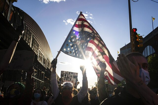 A man holds a U.S. flag upside down, a sign of distress, as protesters march down the street during a solidarity rally for George Floyd, Sunday, May 31, 2020, in the Brooklyn borough of New York. Protests were held throughout the city over the death of Floyd, a black man in police custody in Minneapolis who died after being restrained by police officers on Memorial Day. (AP Photo/Wong Maye-E)