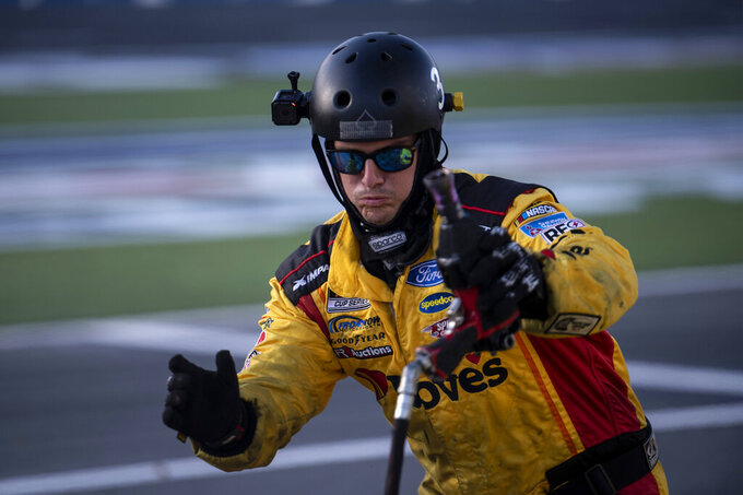 A crew member for Michael McDowell (34) hurries to complete a pit stop during a NASCAR Cup Series auto racing race at Charlotte Motor Speedway, Monday, Oct. 11, 2021, in Concord, N.C. (AP Photo/Matt Kelley)