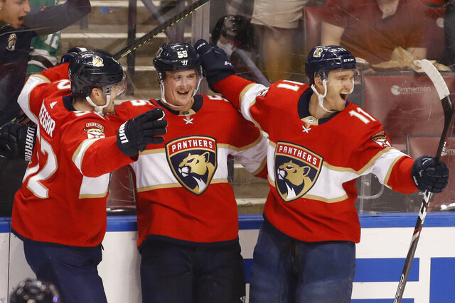 Florida Panthers' Noel Acciari, center, celebrates with teammates MacKenzie Weegar, left, and Jonathan Huberdeau after scoring a goal during the second period of the team's NHL hockey game against the Dallas Stars, Friday, Dec. 20, 2019, in Sunrise, Fla. (AP Photo/Luis M. Alvarez)