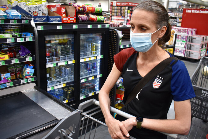 Crystal Dvorak shops at WinCo Foods, Saturday, May, 7, 2021, in Billings, Mont. Dvorak recently lost her job as an audiologist. The day Montana Gov. Greg Gianforte announced the $300 benefit would end June 27 was Dvorak's second day of unemployment. (AP Photo/Matthew Brown)