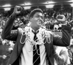 "FILE - In this March 1, 1980, file photo, Georgetown University basketball coach John Thompson raises his hands in victory after fans placed the net around his neck in Providence, R.I., after Georgetown defeated Syracuse University 87-81 to win the Big East basketball championship. John Thompson, the imposing Hall of Famer who turned Georgetown into a ""Hoya Paranoia"" powerhouse and became the first Black coach to lead a team to the NCAA men's basketball championship, has died. He was 78 His death was announced in a family statement Monday., Aug. 31, 2020. No details were disclosed.(Anestis Diakopoulos/Providence Journal via AP, FIle)"