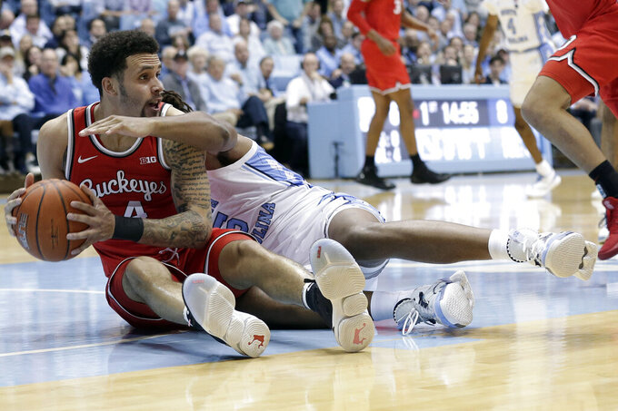 Ohio State guard Duane Washington Jr., left, holds the ball while North Carolina forward Garrison Brooks, right, reaches in during the first half of an NCAA college basketball game in Chapel Hill, N.C., Wednesday, Dec. 4, 2019. (AP Photo/Gerry Broome)