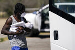 A migrant holds a baby while boarding a bus to Houston at a humanitarian center after they were released from United States Border Patrol upon crossing the Rio Grande and turning themselves in seeking asylum, Wednesday, Sept. 22, 2021, in Del Rio, Texas. (AP Photo/Julio Cortez)