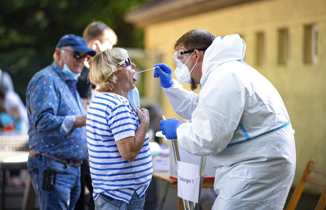 A member of the Bundeswehr takes a coronavirus test on a woman from Warendorf at a corona smear site in Oelde, Germany, Thursday, June 25, 2020 Because of the corona outbreak at the meat producer T'nnies in Rheda-Wiedenbr'ck, many people from the area cannot easily escape on holiday: In several popular regions at home and abroad, negative tests are demanded of them. (Guido Kirchner/dpa via AP)