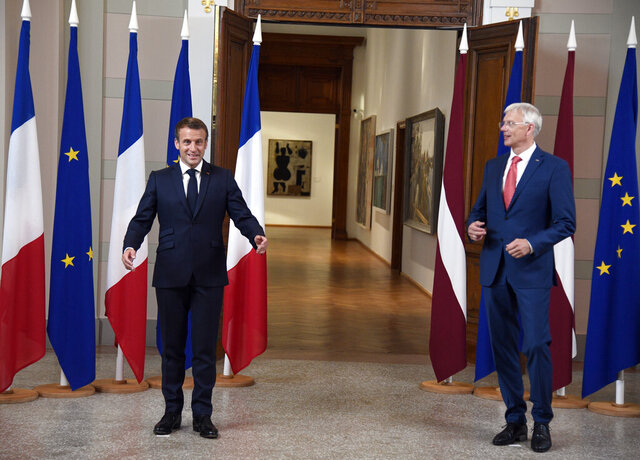 Latvian Prime Minister Krisjanis Karins, right, and French President Emmanuel Macron pose for a photo prior to their meeting at the National Museum of Arts in Riga, Latvia, Wednesday, Sept. 30, 2020. (AP Photo/Roman Koksarov)