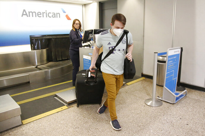 FILE - In this April 30, 2020 file photo, Ethan Cale walks from the American Airlines ticket counter in Salt Lake City.   American Airlines is planning to drop flights to up to 30 smaller U.S. cities if a federal requirement to continue those flights expires at the end of next month, an airline official familiar with the matter said Thursday, Aug. 13.  (AP Photo/Rick Bowmer)