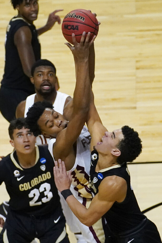 Florida State guard Scottie Barnes, left, goes for a loose ball with Colorado guard Maddox Daniels, right, as Colorado forward Tristan da Silva (23) looks on during the first half of a second-round game in the NCAA college basketball tournament at Farmers Coliseum in Indianapolis, Monday, March 22, 2021. (AP Photo/Charles Rex Arbogast)