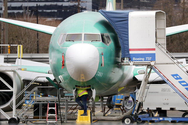 A worker looks up underneath a Boeing 737 MAX jet Monday, Dec. 16, 2019, in Renton, Wash. Shares of Boeing fell before the opening bell on a report that the company may cut production of its troubled 737 MAX or even end production all together. (AP Photo/Elaine Thompson)