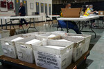 FILE - In this Sept. 3, 2020, file photo, workers prepare absentee ballots for mailing at the Wake County Board of Elections in Raleigh, N.C. The coronavirus pandemic is forcing millions of American voters worried about their health to scramble to vote by mail for the first time. But a requirement in a handful of states, including presidential battleground North Carolina and Wisconsin, that a witness or notary public sign a ballot envelope is tripping up some voters early. (AP Photo/Gerry Broome)