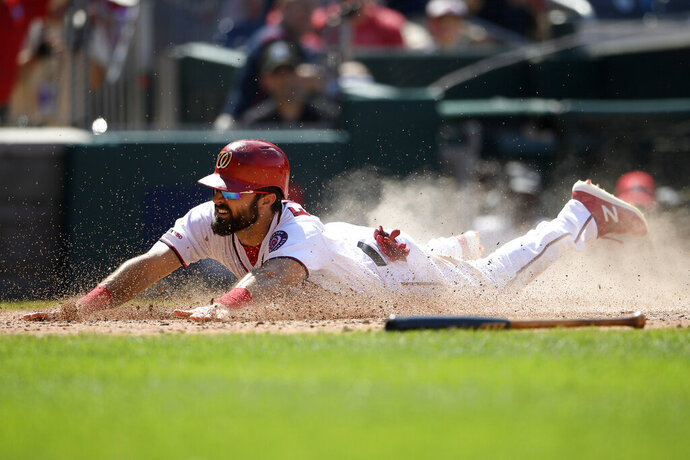 Washington Nationals' Adam Eaton continues his slide as he scored a run on a double by Anthony Rendon against during the eighth inning of a baseball game against the Kansas City Royals, Sunday, July 7, 2019, in Washington. The Nationals won 5-2. (AP Photo/Nick Wass)