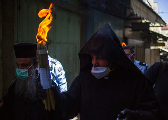 An Orthodox clergyman holds holy fire to transfer to predominantly Orthodox countries from the Church of the Holy Sepulchre, traditionally believed by many Christians to be the site of the crucifixion and burial of Jesus Christ, in Jerusalem's old city after the traditional Holy Fire ceremony was called off amid coronavirus, Saturday, April 18, 2020. A few clergymen on Saturday marked the Holy Fire ceremony as the coronavirus pandemic prevented thousands of Orthodox Christians from participating in one of their most ancient and mysterious rituals at the Jerusalem church marking the site of Jesus' tomb. (AP Photo/Ariel Schalit)