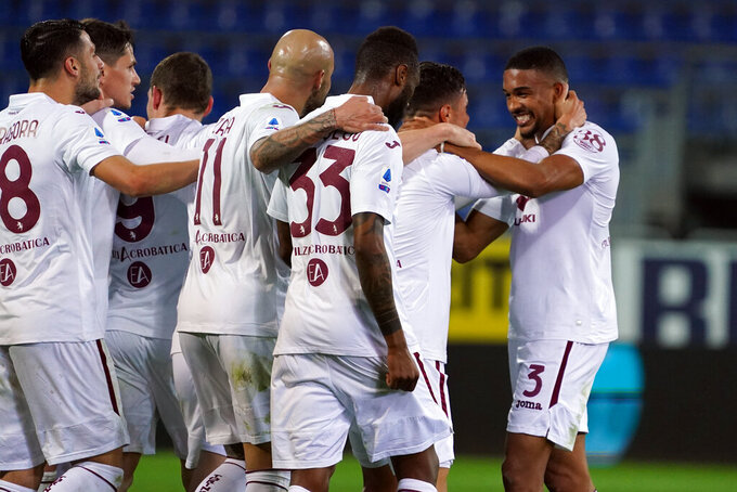 Torino's Gleison Bremer, right, celebrates with teammates after scoring a goal during a Serie A soccer match between Cagliari and Torino, in Cagliari's Sardegna Arena stadium, Italy, Friday, Feb. 19, 2021. (Alessandro Tocco/LaPresse via AP)