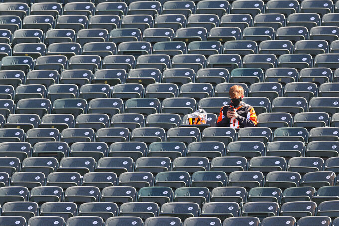 A fan sits in the stands before an NFL football game between the Jacksonville Jaguars and the Cincinnati Bengals in Cincinnati, Sunday, Oct. 4, 2020.  (AP Photo/Aaron Doster)