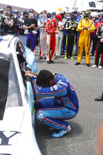 Driver Bubba Wallace, front, is overcome with emotion as he arrives at his car in the pits of the Talladega Superspeedway prior to the start of the NASCAR Cup Series auto race at the Talladega Superspeedway in Talladega Ala., Monday June 22, 2020. In an extraordinary act of solidarity with NASCAR's only Black driver, dozens of drivers pushed the car belonging to Bubba Wallace to the front of the field before Monday's race as FBI agents nearby tried to find out who left a noose in his garage stall over the weekend. (AP Photo/John Bazemore)