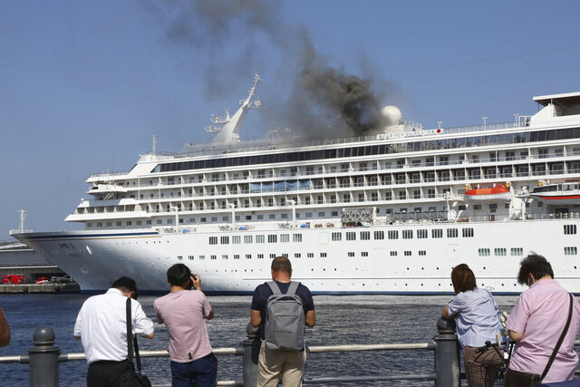 Black smoke rises from the Japanese cruise ship Asuka II docked in Yokohama Port, near Tokyo, Tuesday, June 16, 2020. The local branch of Japan Coast Guard said smoke started on the top floor of the one of Japan's largest cruise ship where dozens of firefighters were battling to extinguish it. The coast guard said there were no reports of injuries. (AP Photo/Koji Sasahara)