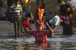 A migrant from Honduras wades across the Rio Grande river to leave Del Rio, Texas and return to Ciudad Acuna, Mexico, early Wednesday, Sept. 22, 2021, to avoid possible deportation from the U.S. (AP Photo/Fernando Llano)