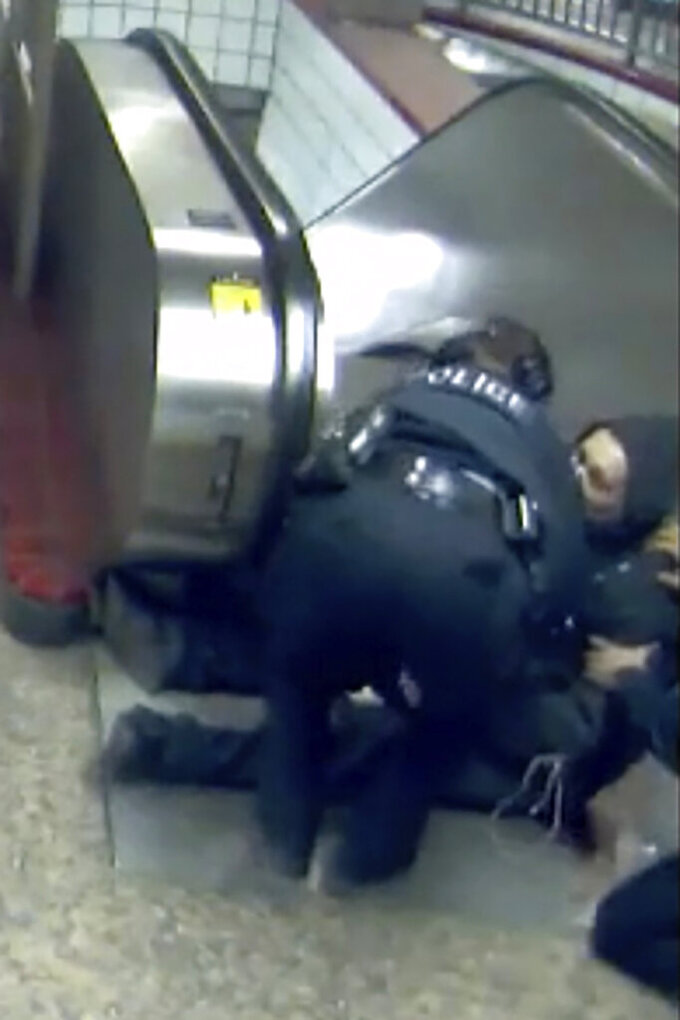 FILE - In this Feb. 28, 2020, image from Chicago Transit Authority video provided by the Civilian Office of Police Accountability, police officers attend to Ariel Roman, bottom right, after he was shot by Chicago police in a subway station in Chicago. Chicago Police officer Melvina Bogard, who shot Roman, an unarmed man, in the back as he tried to escape capture by running up an escalator last year has been charged with felony aggravated battery with a firearm and official misconduct, prosecutors said Thursday, Aug. 5, 2021. (Chicago Transit Authority via AP File)