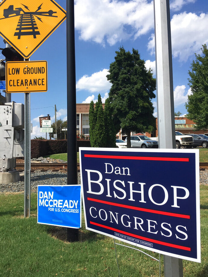 Campaign signs for Republican House candidate Dan Bishop and Democratic House candidate Dan McCready, are shown in in Waxhaw, NC, outside Charlotte, Saturday, Sept. 7, 2019. McCready faces Bishop in a special election for a vacant house seat Tuesday. National Democratic and Republican leaders are breathlessly watching Tuesday's special election for an empty House seat from North Carolina for early clues about next year's presidential and congressional races. But for the two candidates, the race is less glamour than grind.  (AP Photo/Alan Fram)