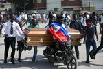 Family and friends transport the coffin that contain the remains of a protester who was recently killed, in Port-au-Prince, Haiti, Tuesday, Nov. 19, 2019. Hundreds of people attended the funerals for people killed during anti-government protests, three of whom were allegedly shot by police while participating in the protests. (AP Photo/Dieu Nalio Chery)