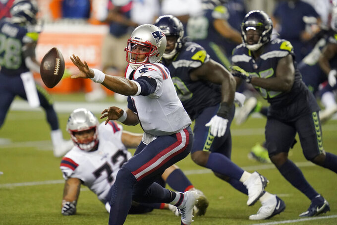 New England Patriots quarterback Cam Newton pitches the ball out during the second half of an NFL football game against the Seattle Seahawks, Sunday, Sept. 20, 2020, in Seattle. (AP Photo/Elaine Thompson)