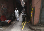 A elderly Muslim man walks by an ill-fated building which caught fire on Sunday in New Delhi, India, Monday, Dec. 9, 2019. Authorities say an electrical short circuit appears to have caused a devastating fire that killed dozens of people in a crowded market area in central New Delhi. Firefighters fought the blaze from 100 yards away because it broke out in one of the area's many alleyways, tangled in electrical wire and too narrow for vehicles to access. (AP Photo/Manish Swarup)
