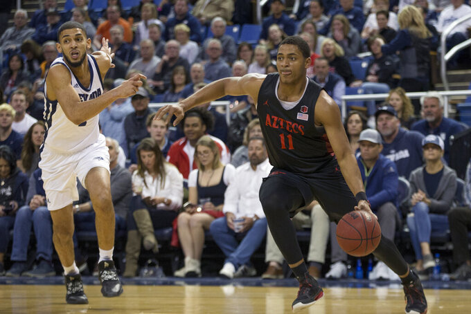 San Diego State forward Matt Mitchell (11) drives past Nevada forward Robby Robinson (1) during the first half of an NCAA college basketball game in Reno, Nev., Saturday, Feb. 29, 2020. (AP Photo/Tom R. Smedes)