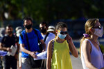 Passengers, wearing face masks to protect against the spread of the new coronavirus, wait in a queue to board a ferry at the port of Piraeus, near Athens, Sunday, Aug. 30, 2020. Greek health officials said Friday that they are expanding for another two weeks a series of domestic health measures, including the obligatory use of masks in most indoors public areas, distancing on beaches and a ban on large gatherings on the occasion of religious festivals. (AP Photo/Michael Varaklas)