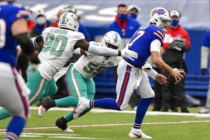 Buffalo Bills quarterback Josh Allen (17) outruns a tackle by Miami Dolphins outside linebackers Shaq Lawson (90) and Jerome Baker (55) during the first half of an NFL football game, Sunday, Jan. 3, 2021, in Orchard Park, N.Y. (AP Photo/Adrian Kraus)
