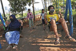 Indonesian children wearing face masks as a precaution against coronavirus outbreak play on swings in Jakarta, Indonesia, Wednesday, Sept. 23, 2020. (AP Photo/Tatan Syuflana)