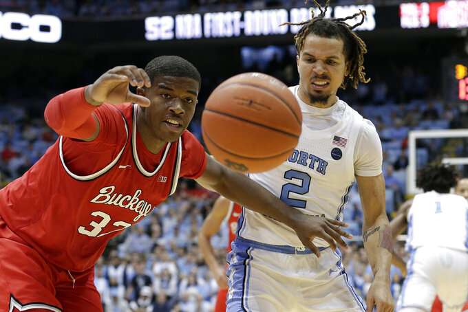 Ohio State forward E.J. Liddell (32) and North Carolina guard Cole Anthony (2) struggle for possession of the ball during the second half of an NCAA college basketball game in Chapel Hill, N.C., Wednesday, Dec. 4, 2019. Ohio State won 74-49. (AP Photo/Gerry Broome)