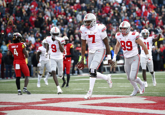 Ohio State quarterback Dwayne Haskins Jr. (7) celebrates his touchdown next to tight end Luke Farrell (89) and wide receiver Binjimen Victor (9) during the overtime of an NCAA football game as Maryland defensive back Darnell Savage Jr. (4) looks on at left, Saturday, Nov. 17, 2018, in College Park, Md. Ohio State won 52-51. (AP Photo/Nick Wass)