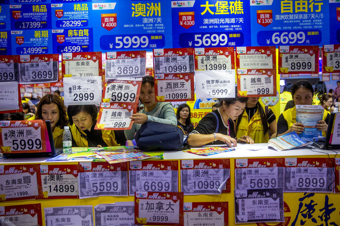 In this March 3, 2018, photo, people check on travel packages offered by travel agencies during the Guangzhou International Travel Fair in Guangzhou in south China's Guangdong province. Travelers in China were blocked from buying plane tickets 17.5 million times last year as a penalty for failing to pay fines or other offenses. The Chinese government reported this week on penalties imposed under a controversial
